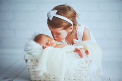 Children sister kisses brother  newborn sleepy  baby on a light. Background Royalty Free Stock Photo