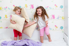 Children sisters play with pillows Royalty Free Stock Photography