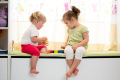 Children sisters play together at home. Children sisters play together indoors Stock Image