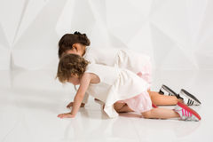 Children sisters play together on white background Stock Image