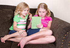Children or sisters using tablet Royalty Free Stock Photo