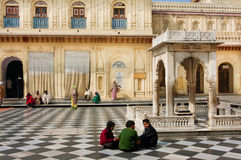 Children sit on the black and white floor of temple Royalty Free Stock Photos
