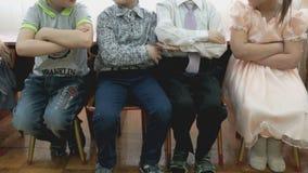 Children sit on chairs at a kindergarten stock video