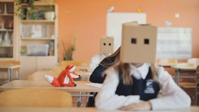 Slow motion. Children sit in classroom at desks with paper boxes on their heads stock video footage