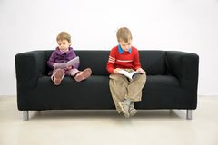 Children sit on couch and read. On home Royalty Free Stock Photos