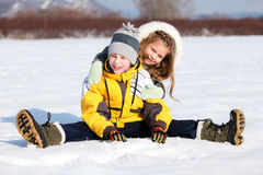 Children sit down in the snow Stock Image