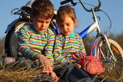 Children sit on dry grass at bicycle Stock Photos
