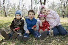 Children sit on the grass in the forest in the spring. Royalty Free Stock Photography