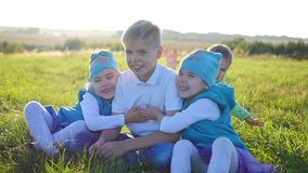 The children sit on the lawn in the park. Laugh, hug and smile. Children`s holiday in the open air. The children sit on the lawn in the park. Children`s holiday stock footage