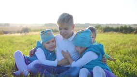 The children sit on the lawn in the Park. Laugh, hug and smile. Children`s holiday in the open air stock video