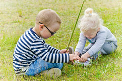 Children  sit on the lawn and what you see in the grass Royalty Free Stock Images