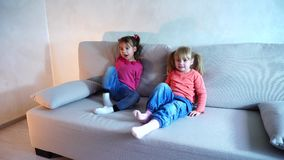 Two sisters playing on sofa in living room. Children sit on light gray sofa in living room, girls play, waving hands and having fun. Interior decorated in stock footage