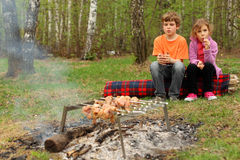 Children sit near campfire with grill and barbecue Royalty Free Stock Photography