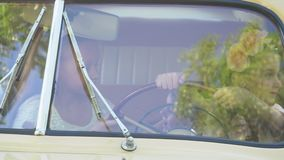 Children sit in the retro car and play about. Small children outdoors. The little girl in a beautiful dress drives the. On this video you can see as the large stock footage