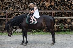 Children sit in rider saddle on animal back. Girls ride on horse on summer day. Friend, companion, friendship. Sport, activity, entertainment. Equine therapy stock photos