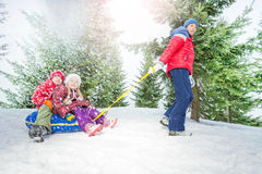 Children sit on snow tube and other boy pulls them Royalty Free Stock Image