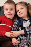 Children sit on sofa holding hands Royalty Free Stock Photos