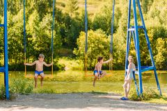 Children sit on a swing on the Playground in the Park stock photography