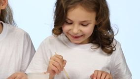 Children sit at the table and decorate the drawings with colors. White background. Slow motion stock video footage
