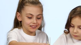 Children sit at the table and decorate the drawings with colors. White background. Slow motion stock footage