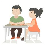 Children sit at the table and play a game. Boy and girl playing at table Stock Photos
