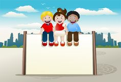 Children sit on top of blank banner sign Royalty Free Stock Image