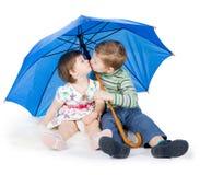 Children  sit under a blue umbrella Stock Photos
