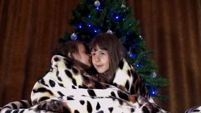 Children sit under a rug near the Christmas tree. Two little girls are covered with a spotted blanket. Two sisters play stock video footage