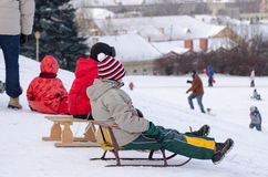 Children sit wooden sledge ready slide from hill Stock Photography