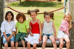 Children siting together in park. Royalty Free Stock Image