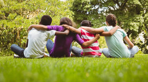Children sitting with arms around at park Royalty Free Stock Images