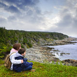 Children sitting at Atlantic coast in Newfoundland Royalty Free Stock Images