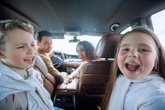 Children sitting in the back seat of the car. Family holiday Royalty Free Stock Photography