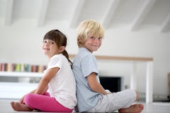 Children sitting back to back Royalty Free Stock Photography