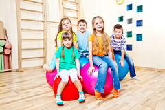 Children sitting on balls Stock Photography