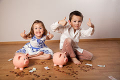 Children sitting among banknotes and showing ok Stock Photo