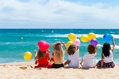 Children sitting on beach with color balloons. Royalty Free Stock Photo