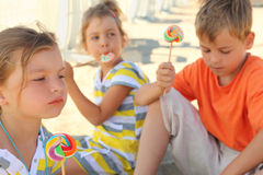 Children sitting on beach and eating lollipops Stock Photography