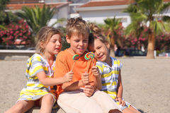 Children sitting on beach with lollipops. Little boy and two girls sitting on beach and holding multicolored lollipops, palms and building Stock Photography