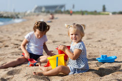 Children sitting on beach Stock Images