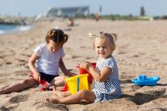 Children sitting on beach stock images