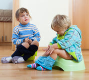Children sitting on bedpans royalty free stock image