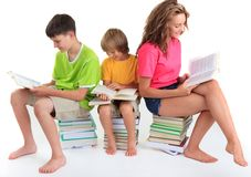 Children sitting on books Stock Images