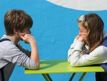 Boy and girl sitting at a table Stock Photo
