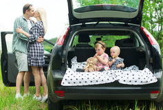 Children sitting in car trunk. Parents stand nearby and kiss. Royalty Free Stock Photos