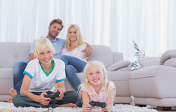 Children sitting on the carpet playing video games. In the living room royalty free stock photo