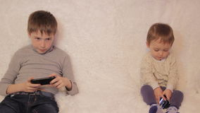 Children sitting on the couch playing on your tablet and phone. To computer games stock footage