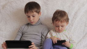 Children sitting on the couch playing on your tablet and phone. To computer games stock video footage