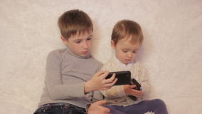 Children sitting on the couch playing on your tablet and phone. To computer games stock video