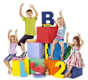 Children sitting at cube. Royalty Free Stock Photos